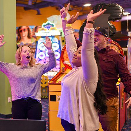 Boondocks - Three people playing an arcade game.